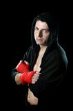 Man in boxing hoodie jumper with hood on head with wrapped hands wrists ready to fight. Young man in boxing hoodie jumper with hood on head wearing hand and Stock Photo