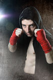 Man in boxing hoodie jumper with hood on head with wrapped hands wrists ready to fight Stock Photo