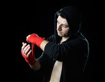 Man in boxing hoodie jumper with hood on head wrapping hands wrists before gym training Royalty Free Stock Photo