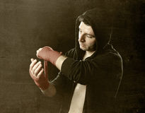 Man in boxing hoodie jumper with hood on head wrapping hands wrists before gym training Royalty Free Stock Photos