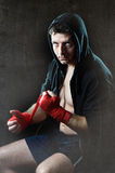 Man in boxing hoodie jumper with hood on head wrapping hands wrists before gym training Stock Image