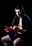 Man in boxing hoodie jumper with hood on head wrapping hands wrists before gym training Stock Photography