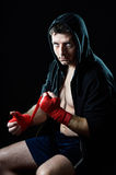 Man in boxing hoodie jumper with hood on head wrapping hands wrists before gym training Royalty Free Stock Image
