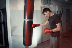 Man boxing strikes punching bag, angry, tense. Dark Stock Image