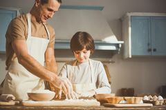 Glad father and son cooking baked sweets. Man and boy in aprons standing at the kitchen table. They powdering processing board. Copy space in right side Stock Photos
