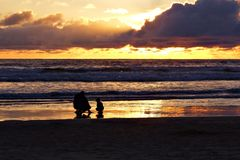 Man and boy on beach at sunset. A man and boy crouch in silhouette on an Oregon beach at sunset Royalty Free Stock Photo
