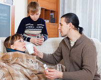Man and boy caring for sick mother Stock Photos