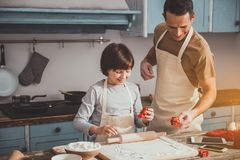 Man and boy doing delicious bakery. Content father and his son making biscuits. They holding cookies cutters and smiling. Copy space in left side Stock Photography