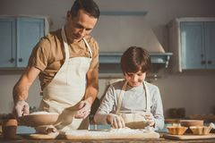 Man and boy doing dough for baking. Satisfied father and son preparing pastry in conjunction. They combining the flour with the egg Stock Image