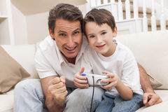 Man Boy Father Son Playing Computer Video Console Game. Man and male boy child, father and son having fun playing video computer console game together using Royalty Free Stock Photos