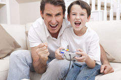 Man & Boy, Father & Son Playing Video Games. Happy man and boy, father and son, having fun playing video console games together, the young boy has the handset Royalty Free Stock Photography