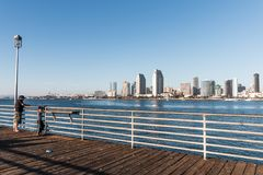 A Man and Boy Fish from Coronado Ferry Landing with Downtown San Diego stock images