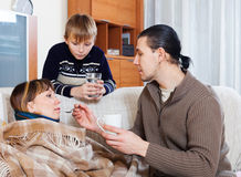 Man and boy giving medicament  to sick  woman Stock Photo
