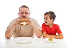 Man and boy with hamburgers Stock Photos