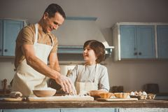Man and boy having fun during cooking. Father and son in aprons preparing bakery together. They sprinkling flour on processing board and laughing. Copy space in Stock Images