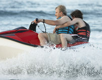 Man and Boy jetskiing in sea. Man and Boy enjoy the wildly jetskiing on red and white jetski in sea to the left Stock Images