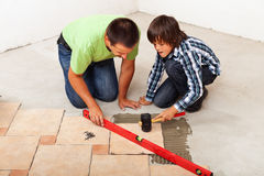 Man and boy laying ceramic floor tiles Royalty Free Stock Photo