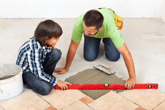 Man and boy laying ceramic floor tiles together Stock Images