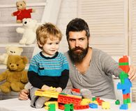 Man and boy play together. Dad and kid with toys. On wooden background build of plastic blocks. Father and son with happy faces create colorful robot with toy royalty free stock images