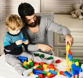 Man and boy play together on wood wall background. Family and childhood concept. Father and son with busy faces create colorful constructions with toy bricks royalty free stock photos