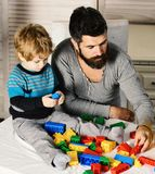 Man and boy play together on wooden wall background. Family and childhood concept. Dad and kid build of plastic blocks. Father and son with serious faces royalty free stock images