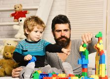 Man and boy play together on wooden wall background. Family and childhood concept. Dad and kid build of plastic blocks. Father and son with happy faces create royalty free stock images