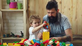 Man and boy play together on wooden wall background. Family and childhood concept. Dad and kid build of plastic blocks. Father and son with serious faces stock video