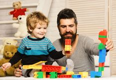 Man and boy play together on wooden wall background. Father and son with happy faces create colorful constructions with toy bricks. Family and childhood stock images