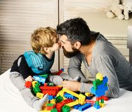 Man and boy play together on wooden wall background. Son kisses father in his nose, making colorful toy bricks constructions. Family and childhood concept. Dad royalty free stock photos