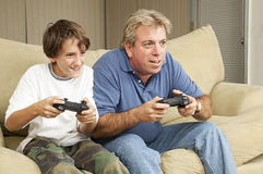 Man and Boy Play Video Games Stock Photos