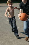 Man and boy playing basketball. Outdoor on street Stock Photography