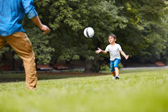 A man and a boy playing football in the park Stock Photo