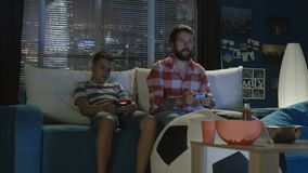 Man and boy playing videogame together. Adult bearded man and teen boy chilling together on sofa and playing videogame with gamepads enjoying evening stock video