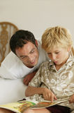 Man and boy reading a book. Young boy reading a book with his father Royalty Free Stock Photography