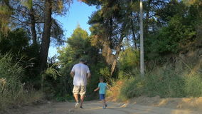 Man and Boy Running down the Country Road. Steadicam slow motion shot of man and boy running down the country road, they are turned backs to the camera stock video footage