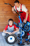 Man and boy servicing a cultivator machine Royalty Free Stock Images