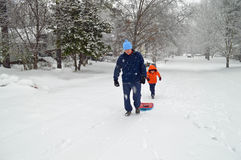 Man and boy with sledge in snow. Snowy landscape with man pulling a sledge along a snow covered avenue between the trees  with a young boy Royalty Free Stock Photos