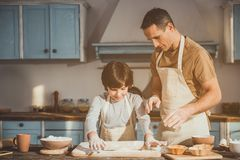Kid and dad making dish for dessert. Man and boy standing in kitchen in aprons. Child rolling out batter while father controlling process Royalty Free Stock Photography