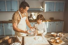 Father teaching son making dessert. Man and boy standing in kitchen. Dad is speaking and gesturing. Cooking equipment and ingredients are on table Stock Photo