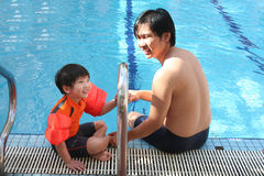 Man & boy at the swimming pool. Man and boy having good time sitting by the swimming pool Royalty Free Stock Photos
