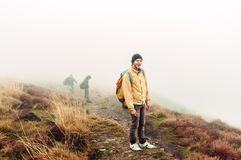 Man, boy traveler standing on a mountain in a yellow jacket. Mountain landscape in the autumn fog. man, boy traveler standing on a mountain in a yellow jacket
