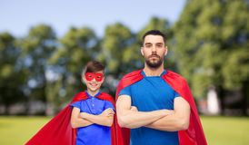 Man and boy wearing mask and red superhero cape Stock Photos