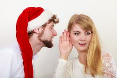 Man in santa hat whispering to woman ear. Man boyfriend in santa claus hat whispering to women girlfriend ear. Gossip couple on gray. Christmas xmas season Stock Photos