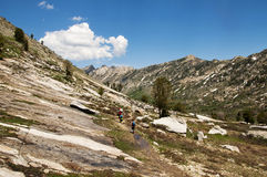 Man and boys hiking in the mountains Royalty Free Stock Images