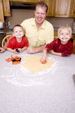 Man and boys making cookies Stock Photos
