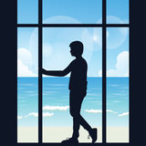 Man boys silhouette alone looking to the sea open area from big window in the dark thinking Royalty Free Stock Images