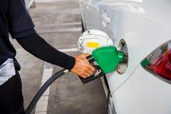Man bränsle för olje- gas för påfyllningen och för fyllning på stationen Bensinstation - tanka Arkivfoto