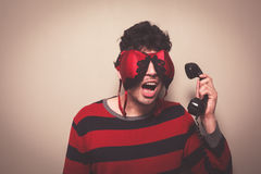 Man with bra on face answering telephone Stock Images