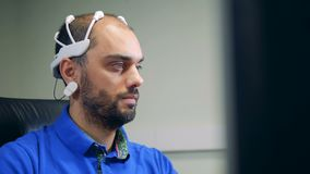 A man in a brainwave scanning headset is operating a computer