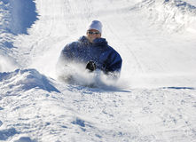 Man Braking While Sledding Down the Hill. Man braking while sledding fast down the hill with snow background Stock Photo
